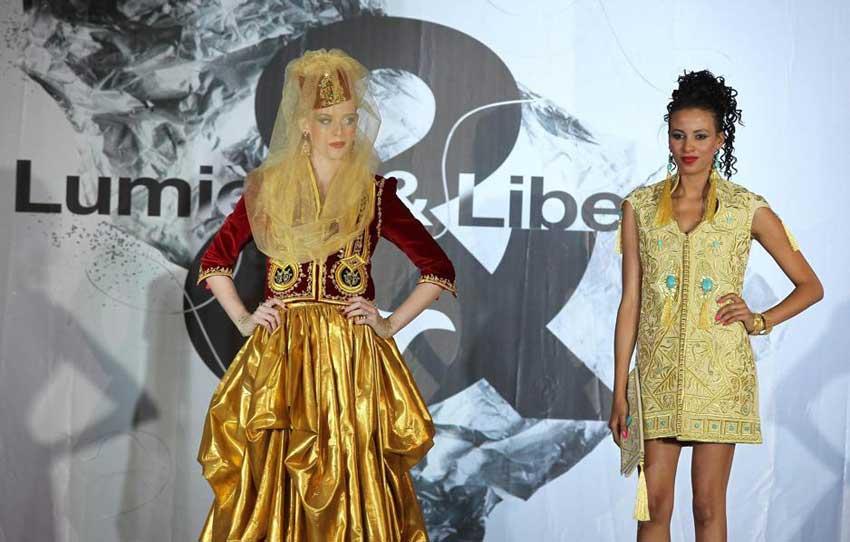 Anche una minigonna alla sfilata di Algeri. Notare gli orecchini maxi coordinati con il vestito. Gioielli etnici anche nella modella inutilmente velata