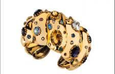 Bracciale d'epoca alla schiava in oro giallo a motivi bombati impreziosito da gemme di tagli e colori diversi tra cui ametiste, quarzi, zaffiri, granati, topazi, rubini, e piccoli diamanti Anni '40 circa