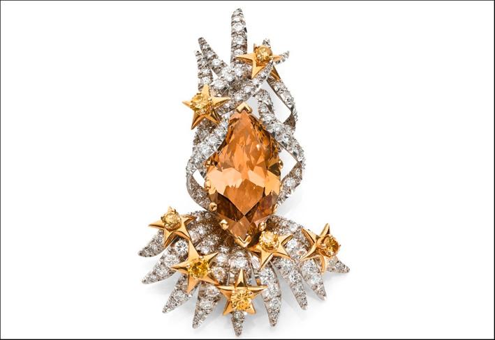 La clip è sostenuta da una corona in platino con diamanti taglio brillante, stelle in oro giallo 18k e diamanti
