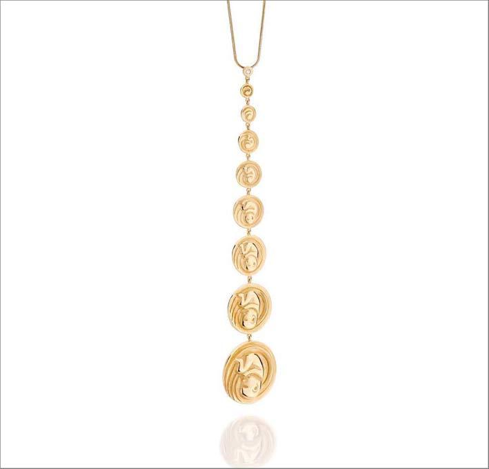 Pendente in oro con medaglie che contengono la forma di un feto che si sviluppa. Sono in onore della maternità
