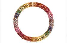 Bracciale decorato con pietre preziose come zaffiri e tsavoriti, con le rondelle di firma del marchio attaccate su una catena in oro rosa da 18 carati, racchiuse da una molla in acciaio inossidabile, che consente flessibilità e movimento