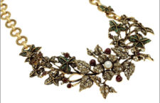 Collier semi-rigido in ottone dorato con ramo e foglie di edera di smeraldo, impreziosite da bacche di granato e fiori di Swarovski dai centrali di perle. Prezzo: 692 euro