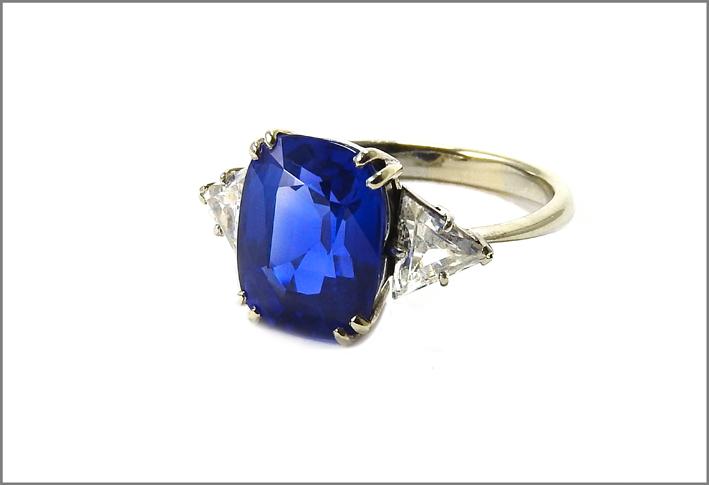 Anello con zaffiro e diamanti taglio triangolare. Lo zaffiro ha taglio a cuscino ct 6,08, misura 17, g 4,5 certificato SSEF n 96222 del 30 ottobre. Stima: 80.000-100.000 euro