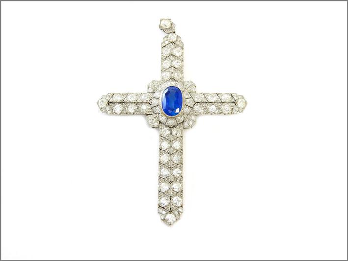Pendente a croce in platino, diamanti  e zaffiro. Inizi XX secolo in scatola originale Massenza, Roma. Diamanti taglio vecchio ct 9 circa complessivi, zaffiro taglio ovale ct 6,90 circa. Stima: 15.000-16.000 euro