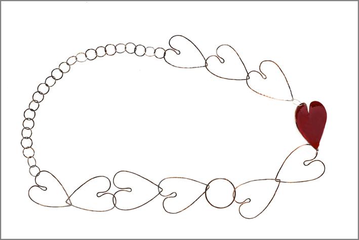 Cuore di Alice, catena formata da cuori vuoti in rame ossidato e battuto e un unico cuore pieno, concavo e laccato di rosso. Lunghezza: 60 cm. Prezzo: 145 euro