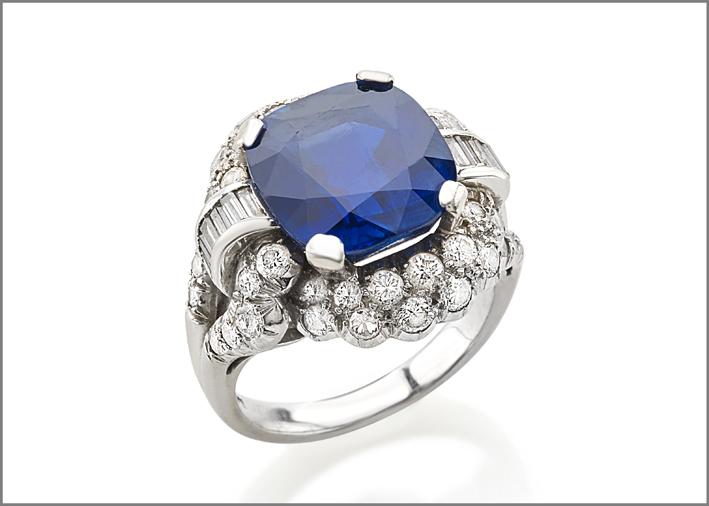 Anello in platino con zaffiro Kashmir taglio cuscino del peso di circa 9 carati contornato da diamanti taglio brillante e baguette per un totale di circa 1ct. Misura 50. Peso 11,10g. Certificato SSEF