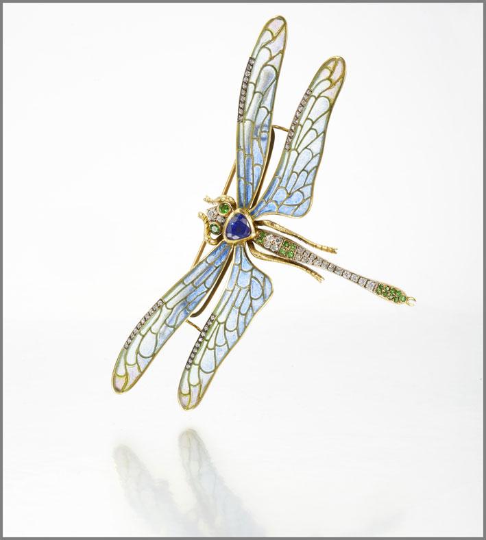Spilla come una libellula, con uno zaffiro a forma di cuore, testa e coda evidenziate con smeraldi rotondi e diamanti, le ali con smalto e con diamanti incastonati, peso lordo circa 26 grammi
