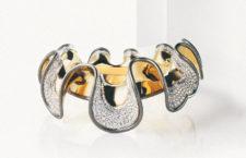 Bloody Mary (1986). Maria Tudor ispira questo collier che ricorda le antiche gorgiere elisabettiane. La variazione cromatica dell'oro brunito e dell'oro giallo, i 1121 diamanti taglio brillante e a taglio baguette, per un totale di 88 carati, interpretano l'intreccio di tessuti e ricami. Una lavorazione molto impegnativa ha modellato l'oro come onde sulle quali sono incastonate le pietre: il metallo sembra una soffice stoffa