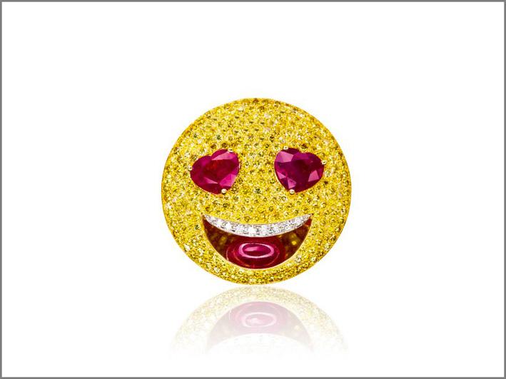 Michele della Valle, spilla emoj .Pavé di diamanti gialli, diamanti bianchi per i denti, rubino cabochon per la lingua, due cuori di rubini come occhi