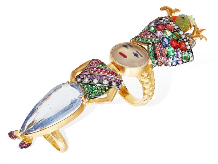 Ring, 19 k gold 36.27 grs, 21 diamonds 0.42 ct, brown diamonds 0.21 ct, 1 white sapphire 12.36 cts, 73 rubys 0.86 ct, 79 fancy sapphires 7.58 cts, 1 peridot 0.49 gr, 1 beryl 3.10 grs