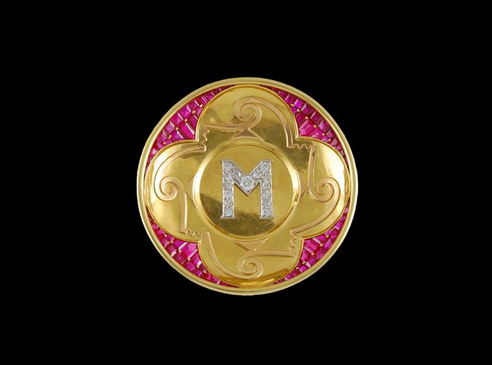 Spilla in oro con al centro la lettera M in pavé