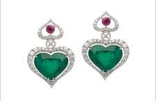 Orecchini con due  smeraldi colombiani a forma di cuore (26.05 carati), oro bianco 18 carati, diamanti bianchi (3,43 carati), e due rubini (di 1,22 carati)