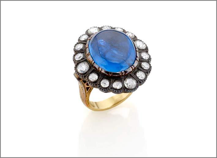 Anello in oro giallo 18 carati e argento con uno zaffiro cabochon ovale del peso di circa 26 ct contornato da diamanti taglio rosette per un totale di circa 1 carato