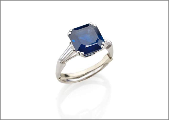 Anello in platino con zaffiro taglio ottagonale a gradini del peso di circa 4 ct con due diamanti taglio tapered lateriali per un totale di circa 0,80 carati