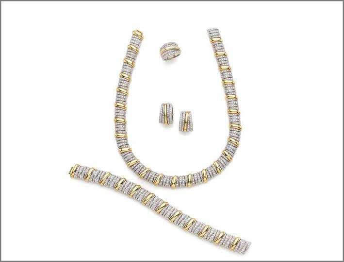 Parure Pomellato composta da collana, bracciale, orecchini e anello in oro bianco e giallo 18 carati con diamanti taglio brillante per complessivi 18,35 carati circa. Corredata da astuccio originale