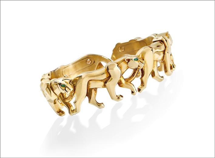 Cartier, bracciale in oro giallo alla schiava formato da una teoria di pantere con occhi in smeraldi